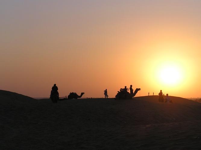 Sun sets beyond the dunes at Sam desert