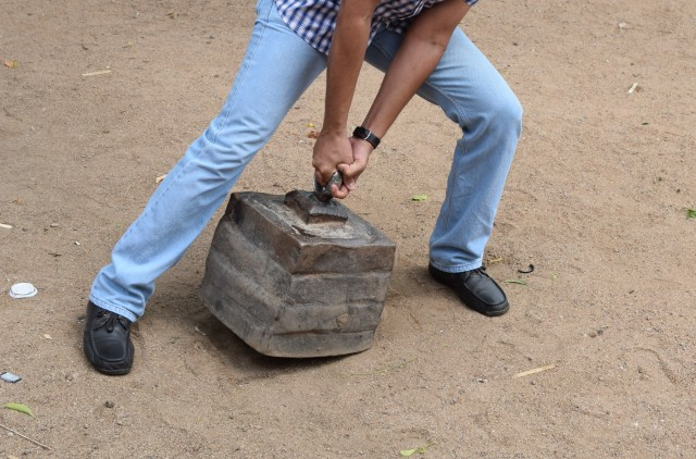 Trying in vain to pick the iron weight