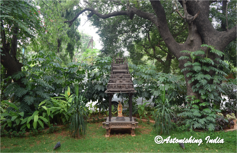 An antique wooden temple replica graces the garden