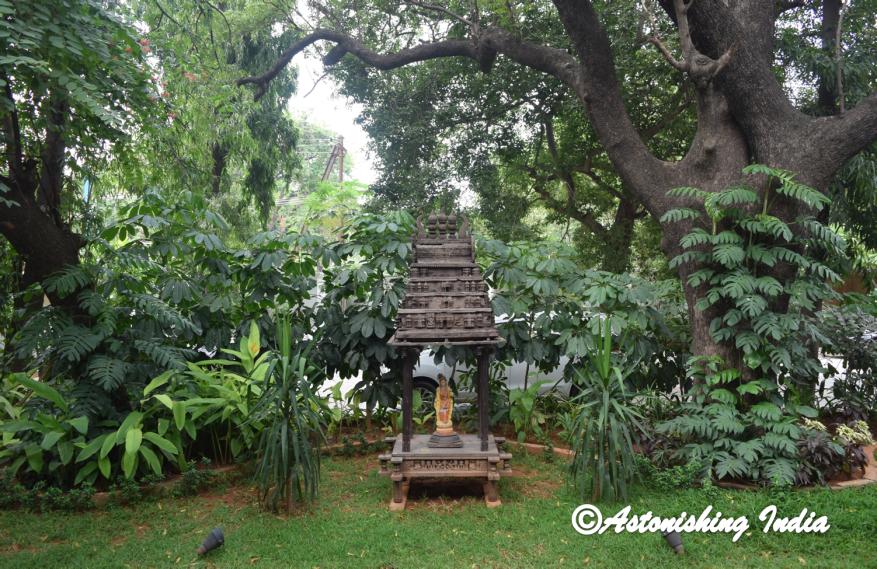 An antique wooden temple replica graces the garden
